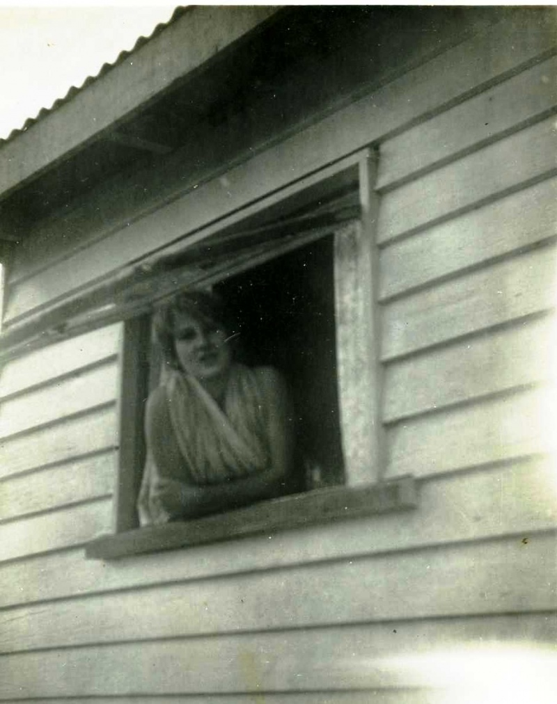Judith looking out of the window of farm house at Mapleton, Queensland around 1960 aged approx 12 to 14